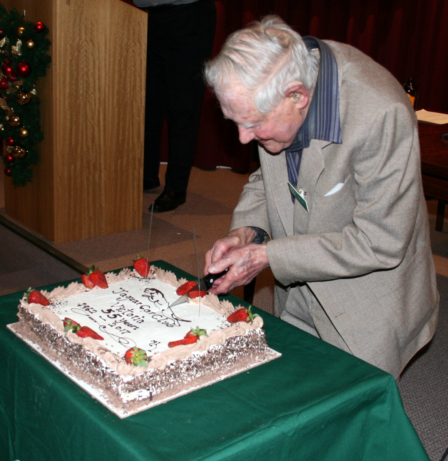 Clubs oldest member Len Coe cuts the cake